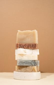 Natürliche bio-selbstpflegeprodukte. turmstapel verschiedener handgemachter seifen auf cremefarbenem hintergrund. spa-accessoires kreative kunstkomposition auf beigem hintergrund