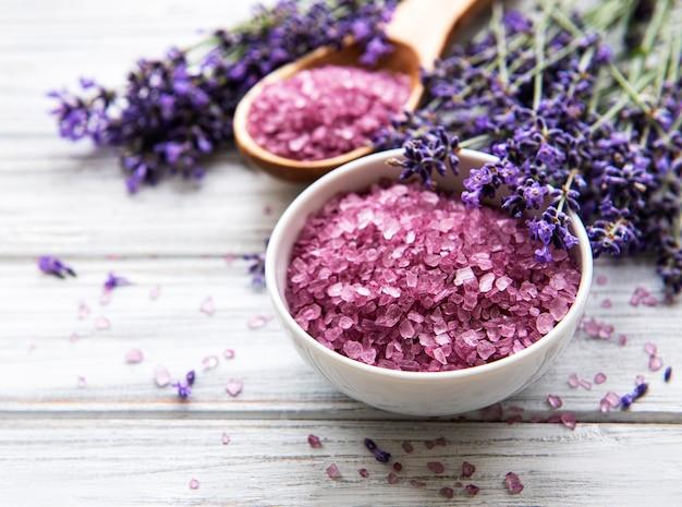 Natürliche bio-spa-kosmetik mit lavendel. flaches badesalz und lavendelblumen auf weißem hölzernem hintergrund. hautpflege, schönheitsbehandlungskonzept