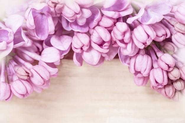 Natürliche blumen mit blühendem rosa flieder nah oben auf unscharfem holz. blumen desktop-hintergrund oder postkarte mit schönen sanften blumen. romantisches weiches sanftes künstlerisches bild.