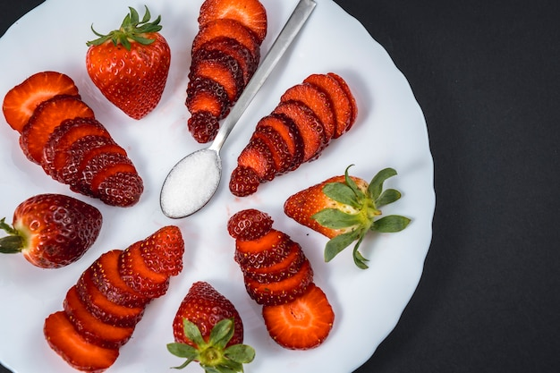 Natürliche erdbeeren auf einem weißen teller mit einem löffel zucker auf schwarz