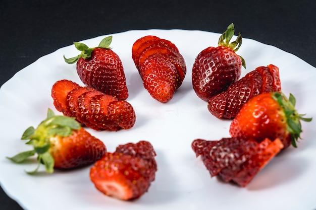Natürliche erdbeeren in scheiben geschnitten auf einem weißen teller auf schwarz