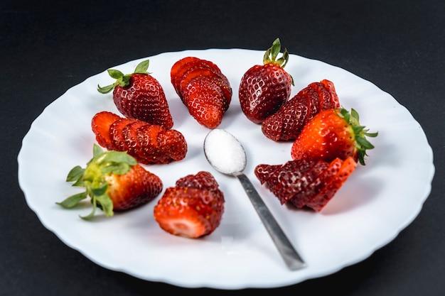 Natürliche erdbeeren in scheiben geschnitten auf einem weißen teller mit einem löffel zucker auf schwarz