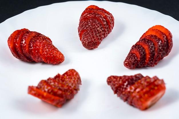 Natürliche erdbeeren in scheiben geschnitten auf einem weißen teller