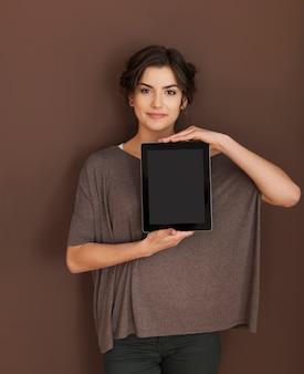 Natürliche frau, die bildschirm des digitalen tabletts zeigt