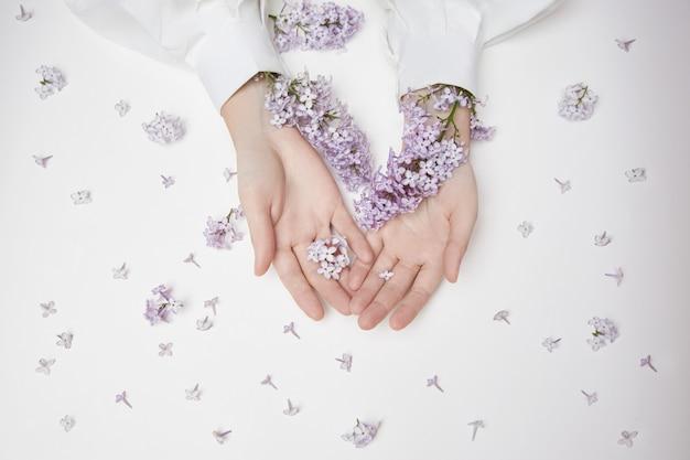 Natürliche frauenkosmetik für hände aus lila blüten und blütenblättern.