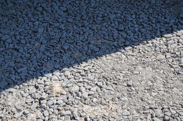 Natürliche graue granitsplitt, macadam, schutt oder schotter hintergrund draufsicht. makrofoto von broken stone oder crushed rock textur mit platz für text