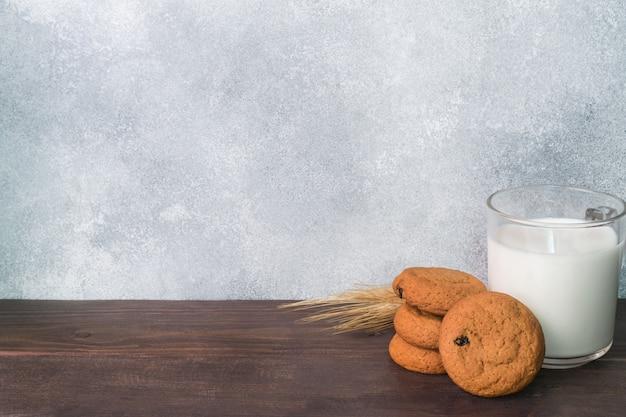 Natürliche hafermehlplätzchen und ein glas milch auf einem hölzernen hintergrund