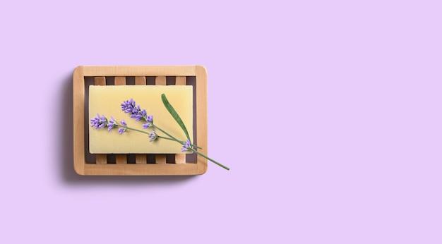 Natürliche hausgemachte lavendelseife mit lavendelblüten auf hölzerner seifenschale auf lila hintergrund.