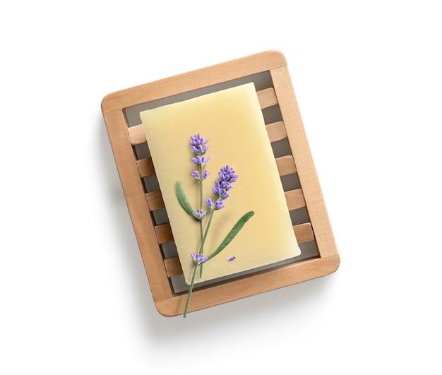Natürliche hausgemachte lavendelseife mit lavendelblüten auf hölzerner seifenschale auf weißem hintergrund.