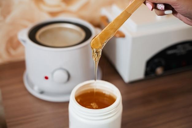 Natürliche heiße zuckerpaste für enthaarung in einem glas und auf einer hölzernen spachtel in den händen eines frauenkosmetikers