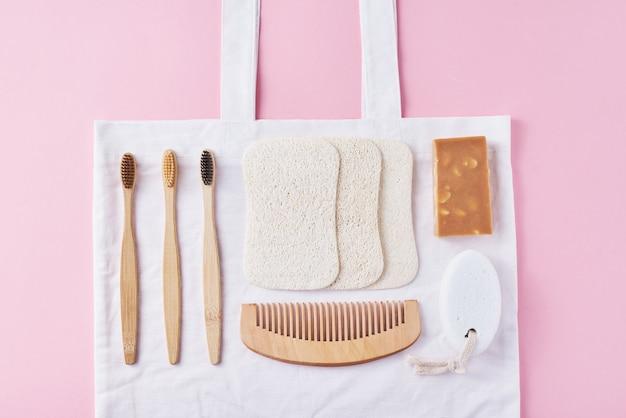 Natürliche hölzerne umweltfreundliche produkte der körperpflege auf einer draufsicht der rosa, flachen lage. bambuszahnbürsten, holzkamm, seife, schwamm und natürliche waschlappen. kein verlust