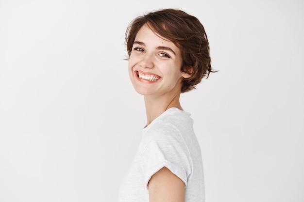 Natürliche junge frau mit glücklichem lächeln, kopf drehen und fröhlich aussehend, im t-shirt gegen weiße wand stehend