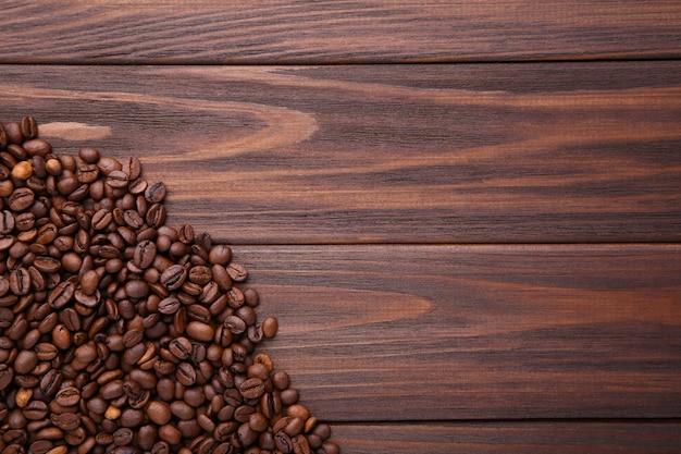 Natürliche kaffeebohnen auf braunem hölzernem