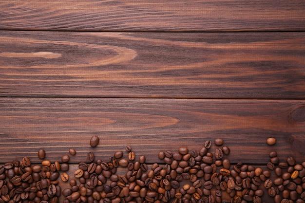 Natürliche kaffeebohnen auf braunem holz