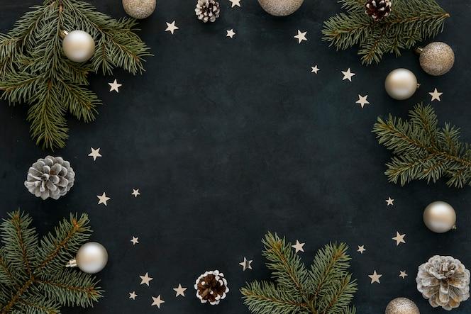 Natürliche kiefernnadeln und weihnachtskugeln auf dunklem hintergrund