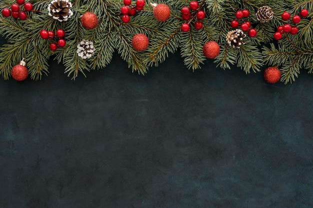 Natürliche kiefernnadeln und weihnachtskugeln mit blumen