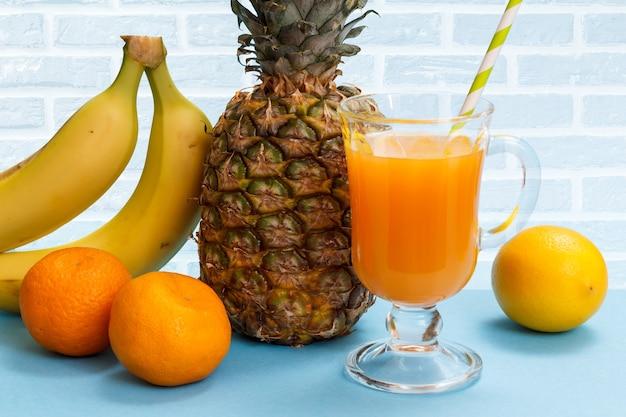 Natürliche komposition mit tropischen früchten. frische ananas, bananen, mandarinen und eine zitrone mit einem glas fruchtsaft.