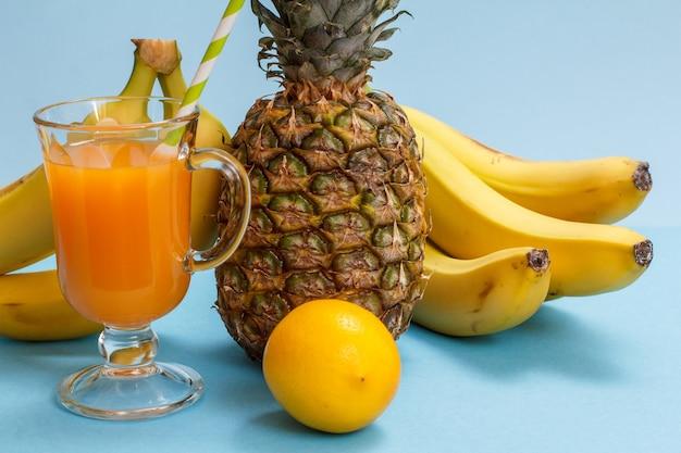 Natürliche komposition mit tropischen früchten. frische ananas, bananen und eine zitrone mit einem glas fruchtsaft auf blauem hintergrund.