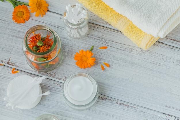 Natürliche kosmetische creme, balsam oder salbe, wattepad, stäbchen und handtücher mit ringelblume trockene und frische blüten auf heller oberfläche