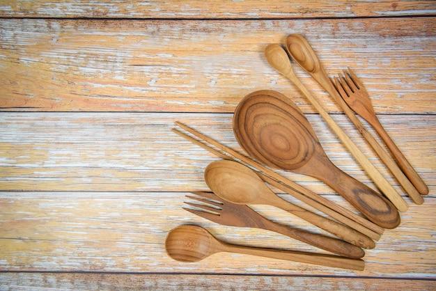 Natürliche küche bearbeitet den hölzernen produkt- / küchengeräthintergrund mit löffelgabelessstäbchenschöpflöffel und nachtischlöffel verschiedene größen auf dem hölzernen plattengegenstandgerät
