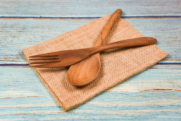 Natürliche küche bearbeitet holzprodukte - küchengeräte mit hölzernem löffel und gabel auf sack im abendtischhintergrund