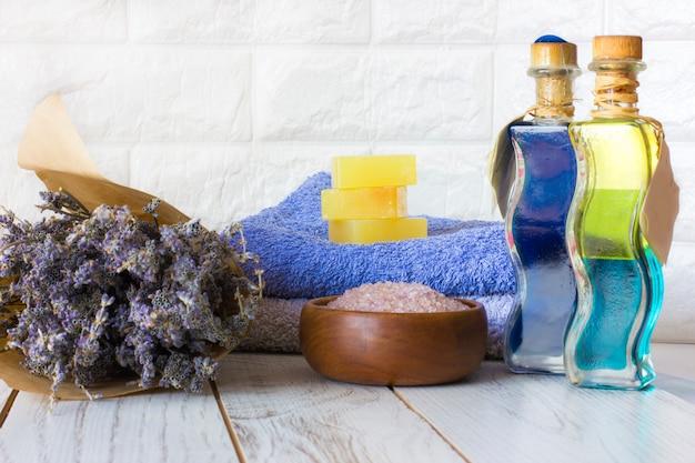 Natürliche lavendelseife und badesalz, französisches öl und tücher auf einem weißen hölzernen hintergrund