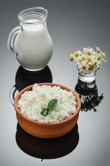 Natürliche milchprodukte, hüttenkäse in einer rustikalen keramikschale. nahaufnahme, selektiver fokus, dunkler hintergrund. bauernquark, natürliches gesundes essen, diätkost