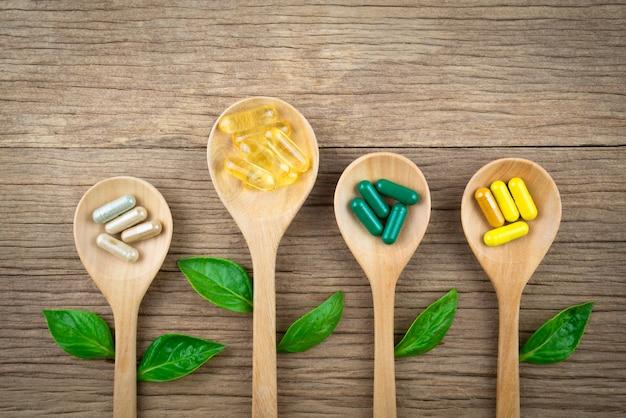 Natürliche nahrungsergänzungsmittel in kapseln aus kräutern auf holz