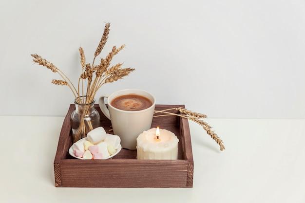 Natürliche öko-wohnkultur mit tasse kaffee marshmallow und kerze auf holztablett