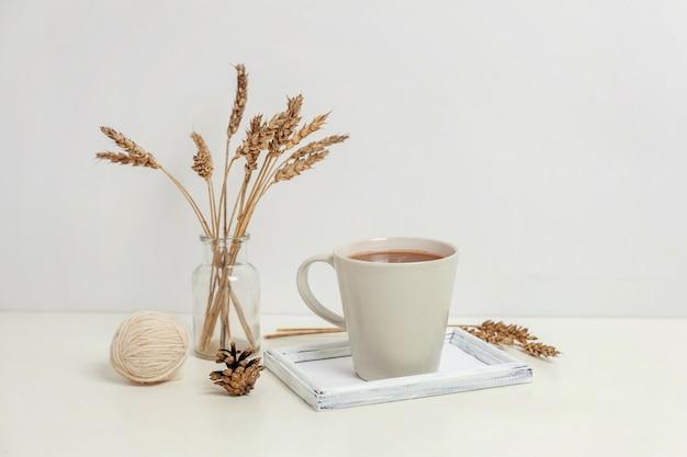 Natürliche öko-wohnkultur mit tasse kaffee und kerze auf holztablett