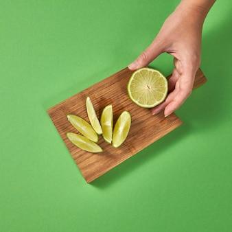 Natürliche organische frische limettenscheiben auf einem holzbrett mit kopierraum. weibliche hände halten ein stück limette. das konzept der gesunden natürlichen vegetarischen ernährung.