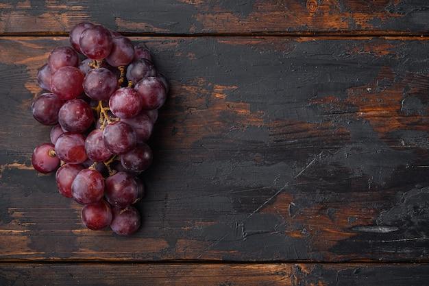 Natürliche organische saftige trauben gesetzt, dunkelrote früchte, auf altem dunklem holztisch, draufsicht flach legen