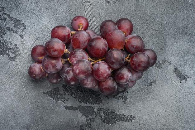 Natürliche organische saftige trauben gesetzt, dunkelrote früchte, auf grauem steintisch, draufsicht flach legen