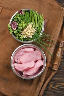 Natürliche rohstoffe für gesunde tierfutterzutaten in einzelnen schalen auf braunem holz.