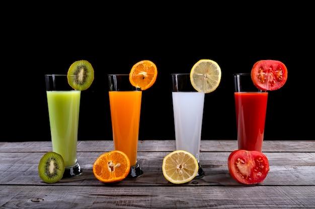 Natürliche säfte der kiwi, der orange, der zitrone und der tomate auf einem schwarzen hintergrund
