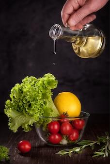 Natürliche salatblätter der produkte, große zitrone und tomaten, in der glasschüssel.
