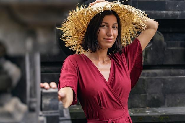 Natürliche schönheit. charmante junge frau, die positivität ausdrückt, während sie einen stilvollen hut zum schießen trägt, balinesische architektur
