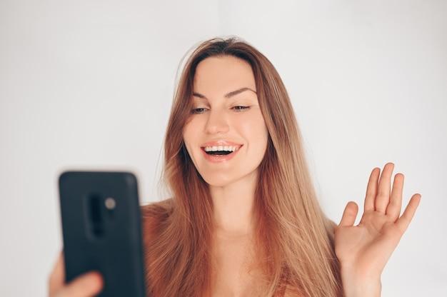 Natürliche schönheit frau mit perfekter haut, die einen videoanruf durch handy lokalisierte weiße wand macht. online-blogger ist live und kommuniziert mit anhängern.