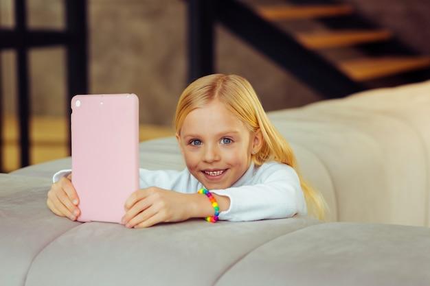 Natürliche schönheit. hübsches langhaariges kind, das ein lächeln auf dem gesicht behält, während es das wochenende zu hause verbringt