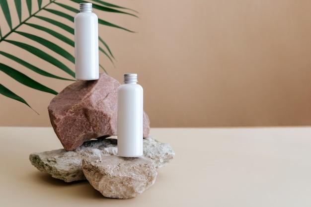Natürliche schönheitskosmetikflaschen weißes mockup-kosmetikprodukt für die hautpflege auf steinsockel mit palmblättern. weiße lotionsflaschen kosmetische minimalistische komposition auf beige hintergrundkopierraum.