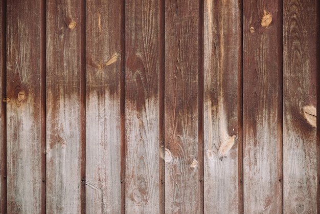 Natürliche struktur der holzoberfläche. detailfragment der natürlichen hölzernen beschaffenheit der weinlese. muster von der ländlichen braunen hölzernen wand, zaun, boden mit copyspace. hintergrund des ungleichen vertikalen planked holzes.