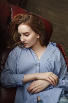 Natürliche süße kaukasische dünne frau mit langen braunen haaren liegt zu hause auf der couch