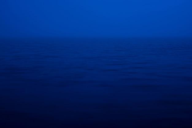 Natürliche textur des tiefblauen ruhigen wassers in der dämmerung schließen. nachtmeer der blauen klassischen farbe. wasserwelligkeit naturhintergrund. meditatives bild des dichten nebels über dem see. weiches licht scheint auf die wasseroberfläche.