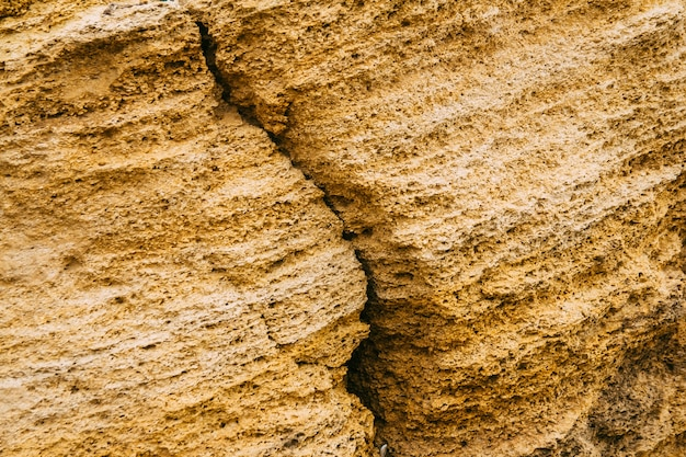 Natürliche textur von gelben felsen. risse und verwitterter natursteinhintergrund.