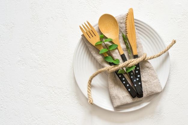 Natürliche tischdekoration mit bambusmessergabel und -löffel, draufsicht mit kopierraum