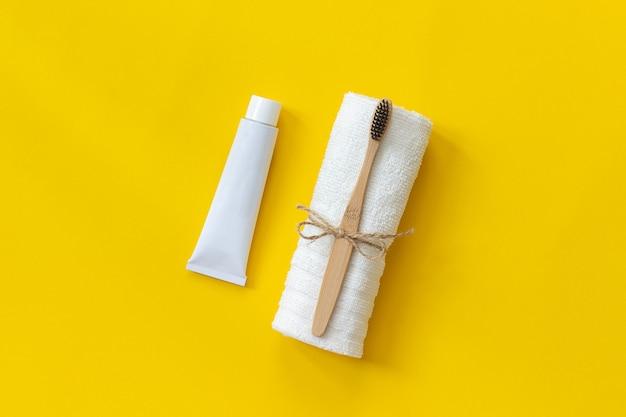 Natürliche umweltfreundliche bambusbürste auf weißem tuch und tube zahnpasta