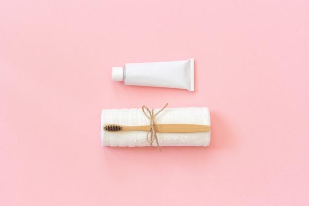 Natürliche umweltfreundliche bambusbürste auf weißem tuch- und zahnpastatube. zum waschen einstellen
