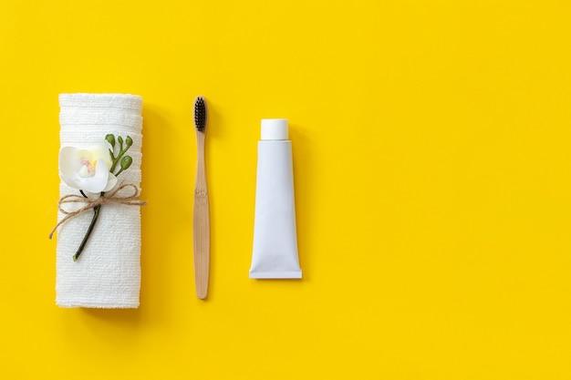 Natürliche umweltfreundliche bambusbürste, weißes handtuch und zahnpastatube. zum waschen einstellen