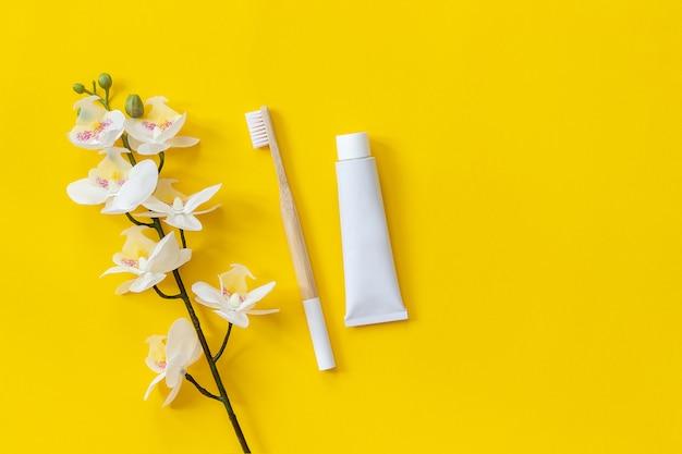 Natürliche umweltfreundliche bambusbürste, zahnpastatube und orhidblume. zum waschen einstellen