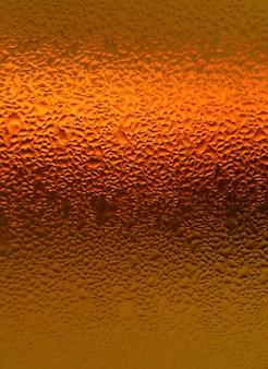 Natürliche wassertröpfchen auf hellorangefarbener flasche, vertikales foto für abstrakten hintergrund mit selektivem fokus
